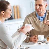 beautiful couple looking at each other and talking during breakfast in morning