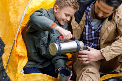 happy son pouring hot drink from thermos to fathers cup white sitting in camping tent