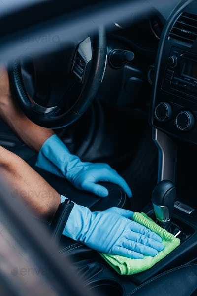 cropped view of car cleaner wiping gear whifter with rag
