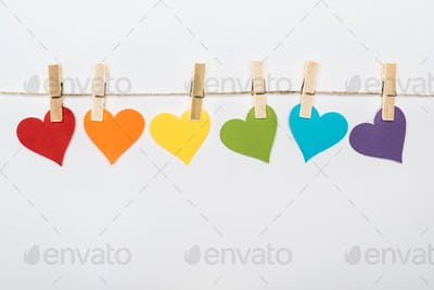 rainbow multicolored paper hearts on rope isolated on white, lgbt concept