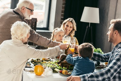 happy family clinking glasses on holiday dinner
