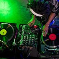 overhead view of professional african american DJ in headphones with sound mixer in nightclub