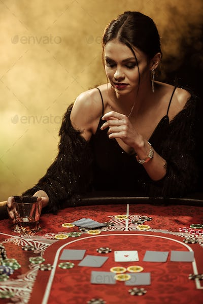 Gorgeous young woman in evening dress sitting at poker table with glass of whisky