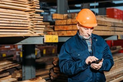 senior builder in helmet using smartphone outside on construction