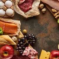 Top view of wooden cutting board with raw fish, meat, poultry, cheese, fruits, vegetables, olive