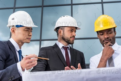 Multiethnic group of professional architects in helmets working with blueprint outside modern