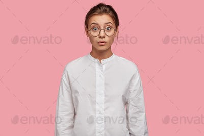 Indoor shot of attractive young woman in round glasses looks with worried expression through glasses