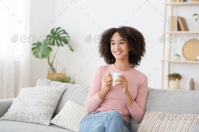 Calm happy woman relaxing and drinking hot drink at home during free time at lockdown