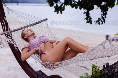 woman in purple bikini lies on hammock by beach on vacation in Thailand