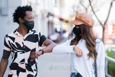 Couple tap each other with elbows to say hello.