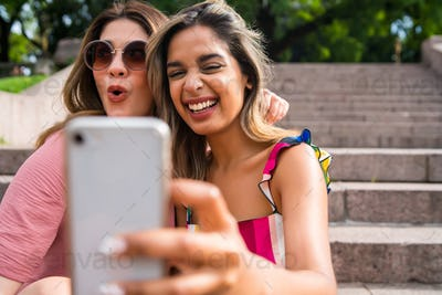 Two friends taking selfie with phone outdoors.
