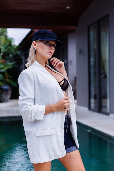 woman in french cap, blazer and shorts outdoor, outside villa, tropical background.