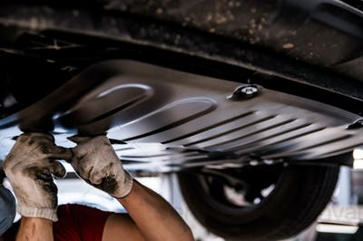 Car mechanic checks engine protection on Service station