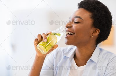 Happy African Woman Drinking Infused Water Posing With Bottle Indoors