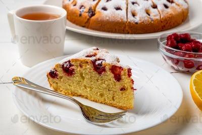 Sliced cherry pie on a plate, and lemon tea. Selective focus, horizontal orientation.