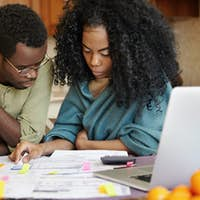 African couple reviewing their finances, analyzing family budget, thinking how to cut off expenses t