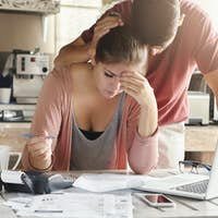 Unhappy couple unable to pay loan on time: stressed female doing paperwork sitting at table with lap