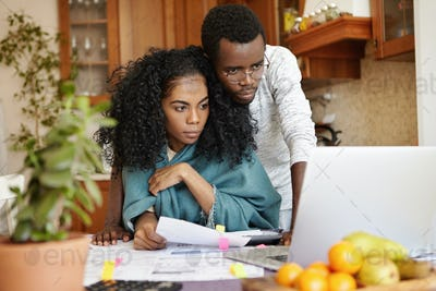 Indoor shot of young dark-skinned couple managing family budget at home, paying gas and electricity