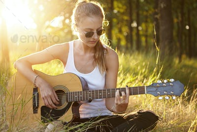 Outdoor portrait of romantic young woman in sunglasses playing guitar while sitting at green grass d