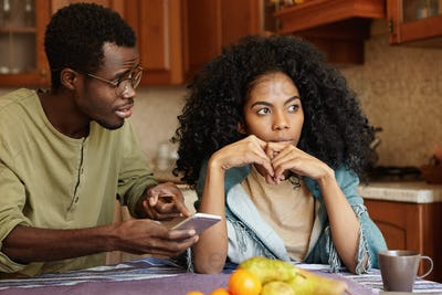 Young Afro-American family fighting in kitchen because of an affair. Man in glasses holding mobile p