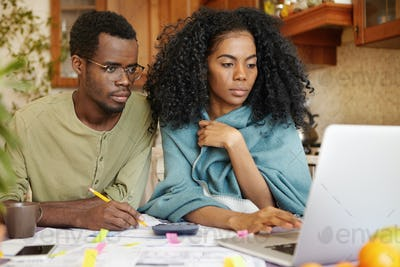 Young African-American family doing paperwork together, sitting at kitchen table with piles of paper