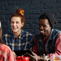 Modern technology, communication and people. Three cheerful students dining at restaurant, talking t