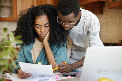 Family, domestic budget, economy and finances concept. Stressed young African-American couple workin