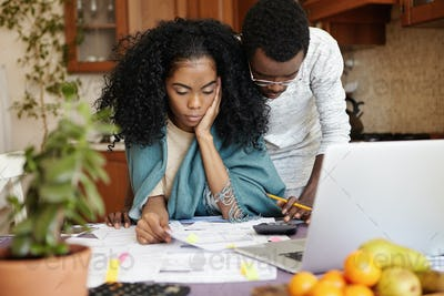Unhappy and stressed young African woman sitting at kitchen table with papers and notebook computer,