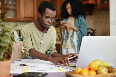 African married couple facing financial troubles. Serious man in glasses calculating domestic expens