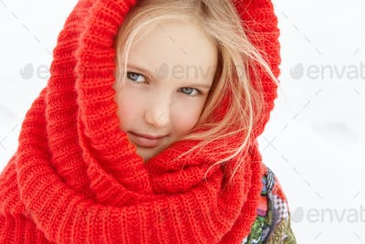 Outdoor view of cute European female child with blonde hair posing outside during short walk in city