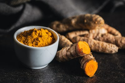 Indian turmeric powder and root. Turmeric spice. Ground turmeric.