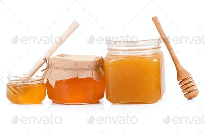 honey in glass jars isolated on white