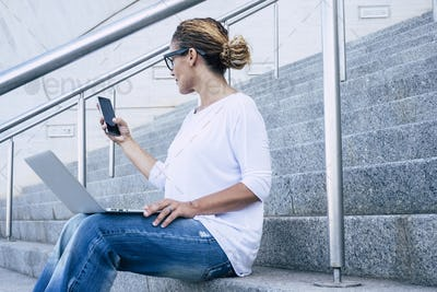 Business woman beautiful female working with phone device and laptop computer outdoor