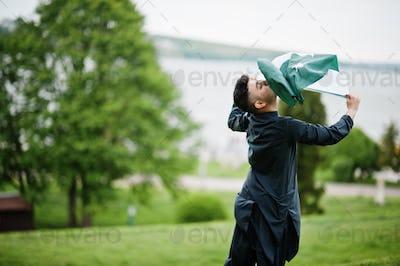 Сonfident pakistani indian muslim arabic boy in grey kameez shalwar suit with Pakistan flag.