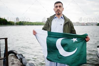 Traditional clothes indian pakistani male portrait hold Pakistan flag.