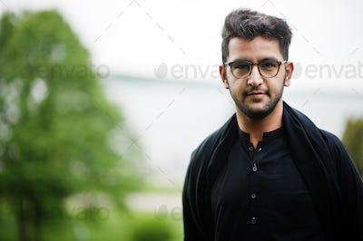 Pakistano bangladesh man wear black traditional clothes and eyeglasses pose outdoor.