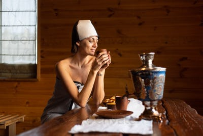 Young woman in a sauna with a cap on her head sits at a table and drinks herbal tea