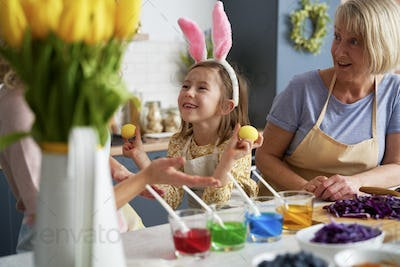 Little girl have fun during coloring Easter eggs with family