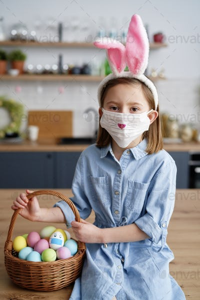 Portrait of girl in a protective mask with Easter basket
