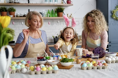 Front view of three generations of woman during coloring eggs