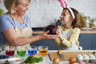 Little girl helping grandmother prepare natural dyes for coloring eggs