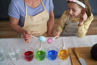 Top view of granddaughter and grandmother dyeing Easter eggs together
