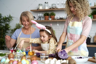 Little girl helping mother and grandma in the kitchen