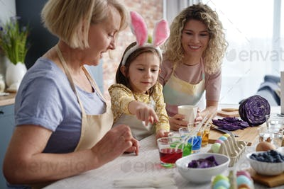 Little girl showing natural egg dyes with her family
