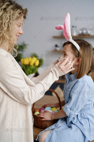 Mother puts a protective mask on her daughter's face