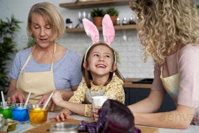 Happy little girl with mother and grandmother during Easter