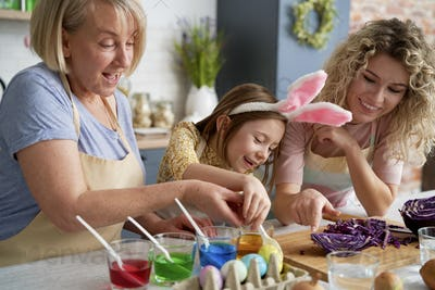 Little girl with mother and grandmother coloring Easter eggs