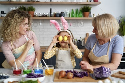 Girl with mother and grandmother have fun during coloring eggs