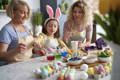 Little girl with mother and grandmother dyeing Easter eggs