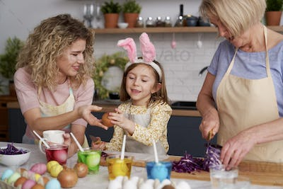 Little girl with family preparing natural dyes for coloring eggs